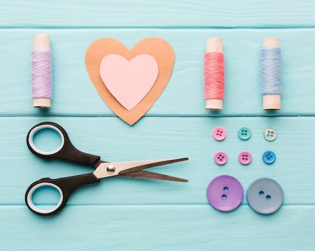 Vista dall'alto del cuore di carta con forniture per cucire per san valentino Foto Gratuite