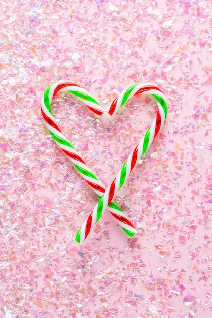 Vista dall'alto del cuore fatto di due lecca-lecca sul rosa con glitter Foto Premium