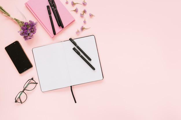 Vista dall'alto del diario; penne; occhiali; cellulare e occhiali su sfondo rosa Foto Gratuite