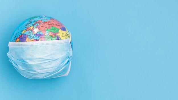 Vista dall'alto del globo indossando maschera medica con spazio di copia Foto Gratuite
