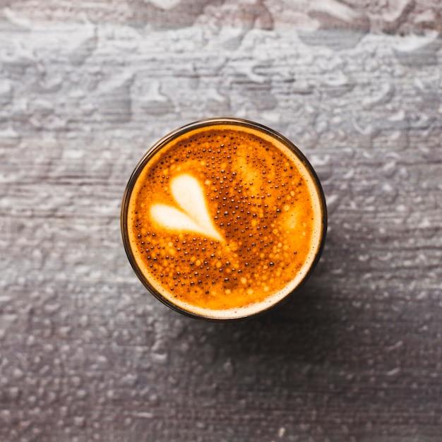 Vista dall'alto del gustoso bicchiere di caffè con latte art su sfondo di gocce d'acqua Foto Gratuite