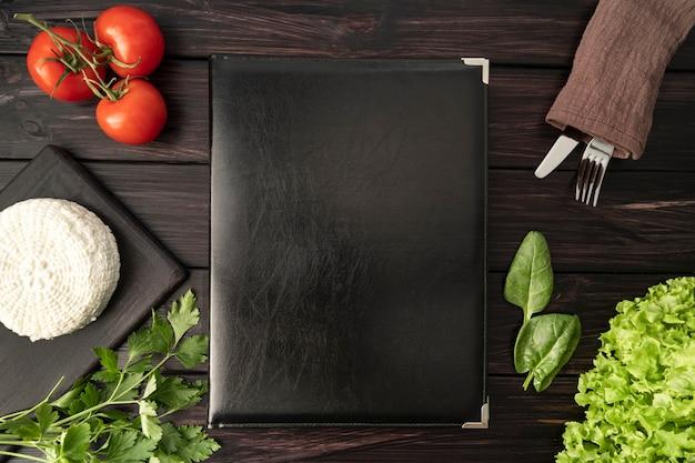 Vista dall'alto del libro menu vuoto con pomodori e posate Foto Gratuite