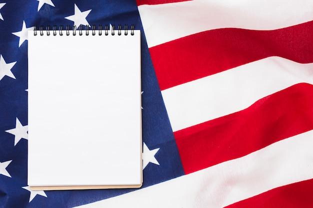 Vista dall'alto del notebook in cima alla bandiera americana Foto Gratuite