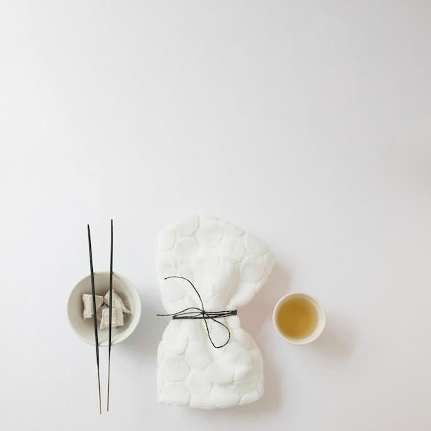 Vista dall'alto del petrolio; bastoncino d'incenso; pietra pomice e tovagliolo legato su sfondo bianco Foto Gratuite