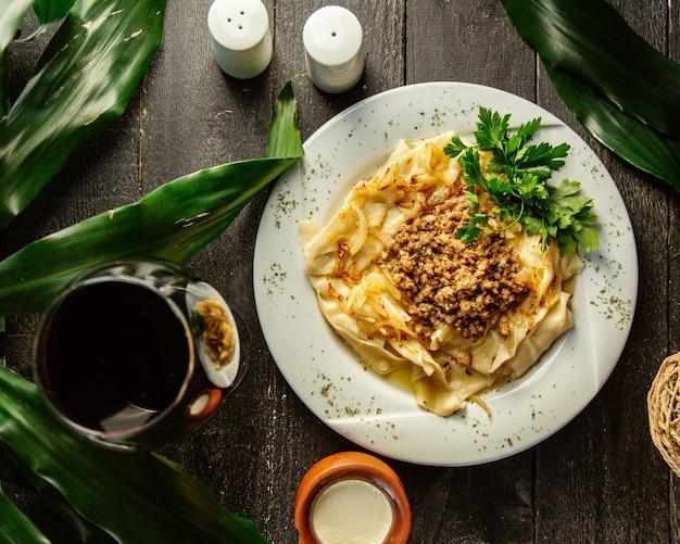 Vista dall'alto del piatto khangal condita con carne macinata e miscela di cipolle Foto Gratuite