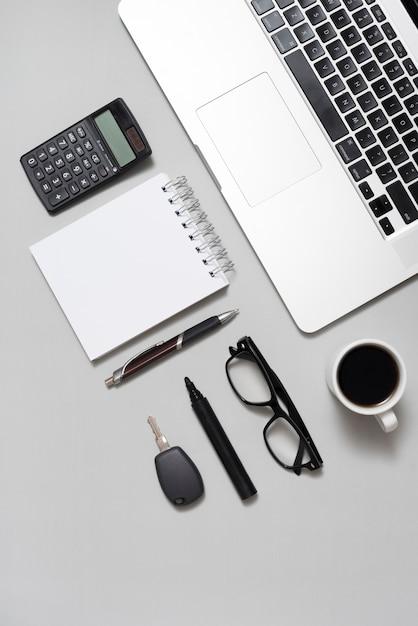 Vista dall'alto del portatile; calcolatrice; blocco note vuoto; occhiali; e tazza di caffè con chiave su sfondo grigio Foto Gratuite