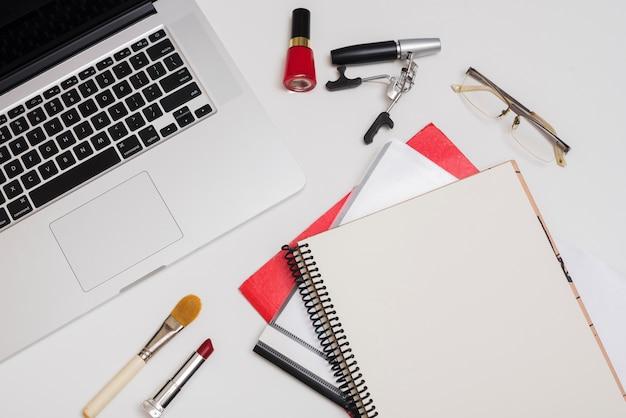 Vista dall'alto del portatile; prodotti cosmetici; cartelle e occhiali sulla scrivania Foto Gratuite