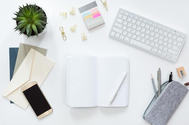Vista dall'alto del posto di lavoro aziendale con tastiera del computer, notebook, fiori in vaso verde e telefono cellulare, piatto laici. Foto Premium