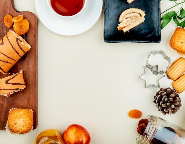 Vista dall'alto del rotolo tagliato e tranciato con prugne secche cupcake sul tagliere con marmellata di tè pesca uvetta biscotti e pigne su bianco con spazio di copia Foto Gratuite