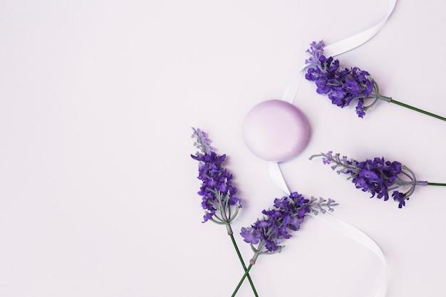 Vista dall'alto del sapone; fiori di lavanda e nastro su sfondo colorato Foto Gratuite