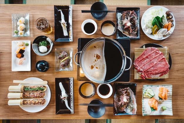 Vista dall'alto del set di shabu tra cui fette rari manzo wagyu a5, base di shabu, salmone, sushi e verdure Foto Premium