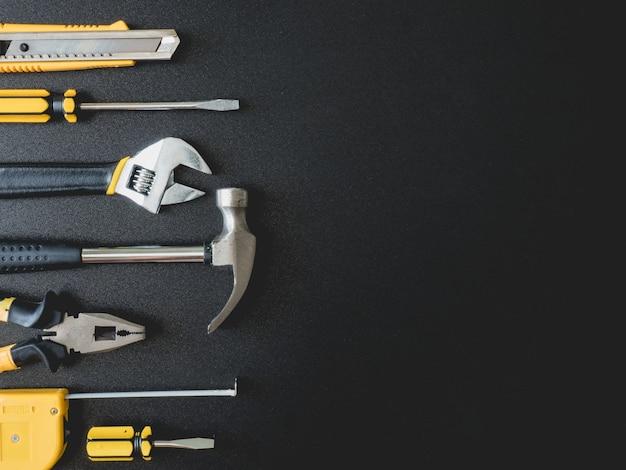 Vista dall'alto del set di strumenti del meccanico su sfondo nero con spazio di copia. Foto Premium