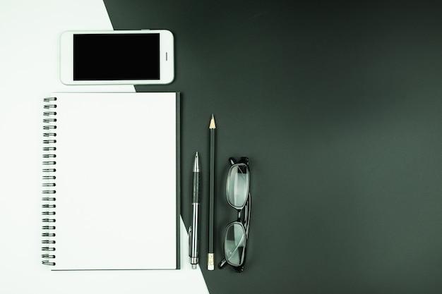 Vista dall'alto del taccuino aperto con smart phone e articoli di cancelleria Foto Premium