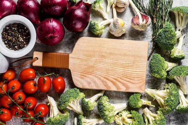 Vista dall'alto del tagliere di legno tra verdure crude. concetto di cucina vegetariana casalinga Foto Premium