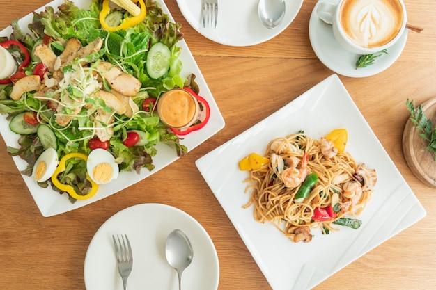 Vista dall'alto del tavolo che viene preparato da un'insalata e spaghetti da mangiare. Foto Premium