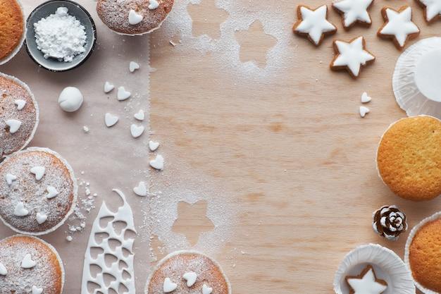 Vista dall'alto del tavolo con muffin zuccherati, glassa fondente e biscotti con stelle di natale su legno chiaro Foto Premium