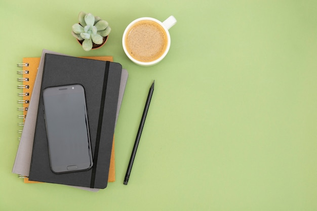 Vista dall'alto del tavolo di lavoro. taccuino chiuso nero, tazza di caffè e smartphone. copia spazio per il testo. design mock up. Foto Premium