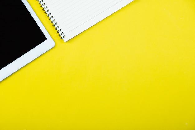 Vista dall'alto del tavolo scrivania ufficio giallo con un sacco di cose su di esso. Foto Gratuite