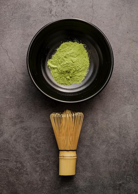 Vista dall'alto del tè matcha in polvere in una ciotola con frusta di bambù Foto Gratuite