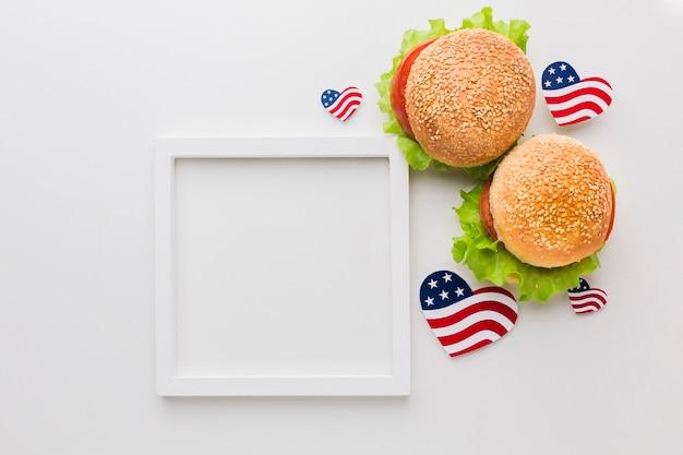 Vista dall'alto del telaio con hamburger e bandiere americane Foto Gratuite