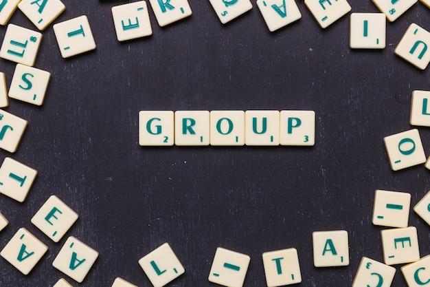 Vista dall'alto del testo di gruppo su lettere scrabble su sfondo nero Foto Gratuite