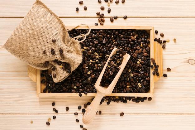 Vista dall'alto del vassoio in legno con chicchi di caffè Foto Gratuite