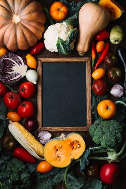 Vista dall'alto deliziosa composizione di verdure con lavagna Foto Gratuite