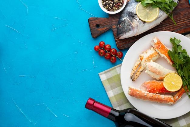 Vista dall'alto deliziosi piatti di pesce con vino Foto Gratuite