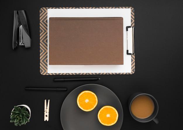 Vista dall'alto dell'area di lavoro con blocco note e piatto di fette d'arancia Foto Gratuite