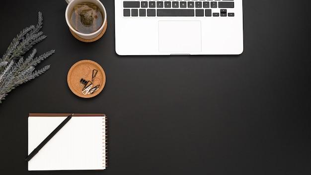 Vista dall'alto dell'area di lavoro con laptop e tazza di tè Foto Gratuite