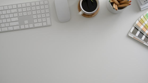 Vista dall'alto dell'area di lavoro minimal designer con computer, matite colorate, campione di colore e spazio di copia Foto Premium