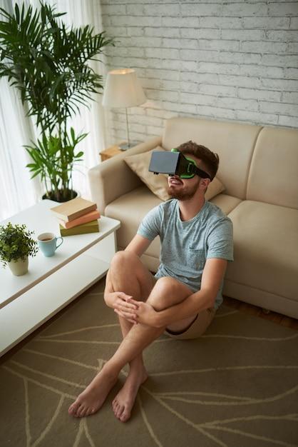 Vista dall'alto dell'uomo seduto sul pavimento del suo salotto godendo il gioco di realtà virtuale Foto Gratuite