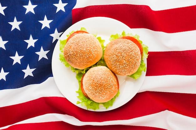 Vista dall'alto della bandiera americana con piatto di hamburger Foto Gratuite