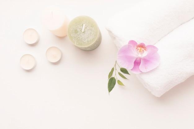 Vista dall'alto della candela con fiore orchidea sopra l'asciugamano arrotolato Foto Gratuite