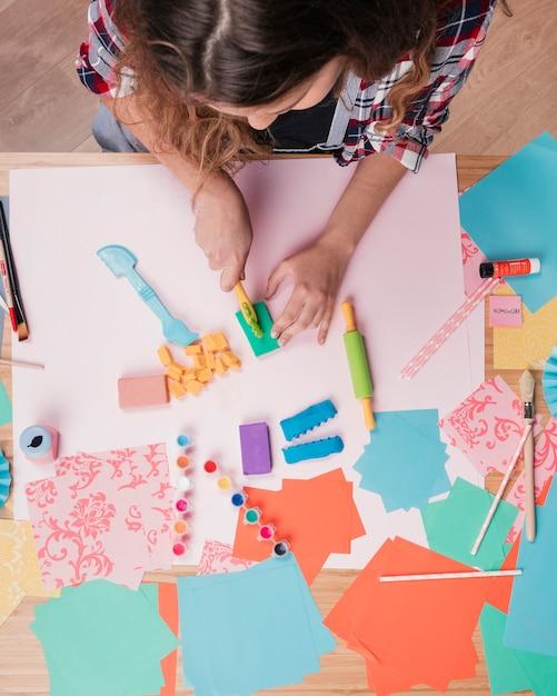 Vista dall'alto della donna che taglia argilla colorata su carta Foto Gratuite