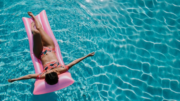 Vista dall'alto della donna rilassante sul materasso in piscina Foto Gratuite
