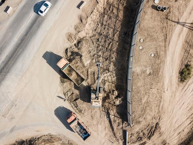 Vista dall'alto della macchina dell'escavatore scavare il terreno e metterlo in autocarro con cassone ribaltabile industriale Foto Premium
