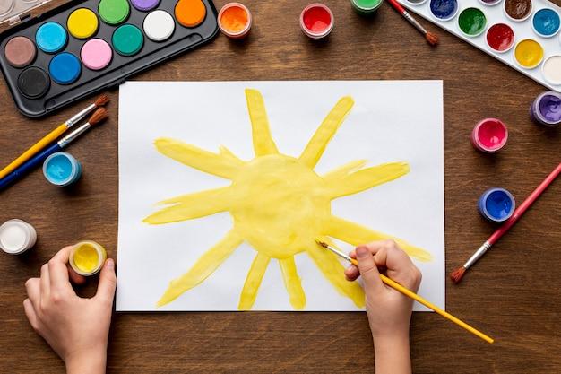 Vista dall'alto della mano che dipinge un sole Foto Gratuite