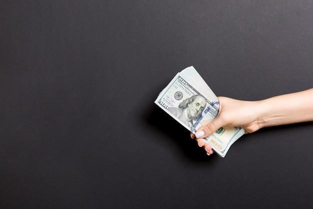 Vista dall'alto della mano dando un centinaio di dollari Foto Premium