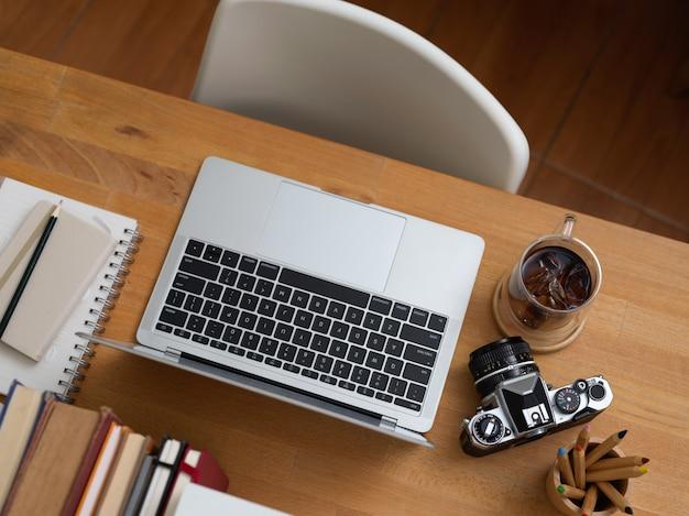 Vista dall'alto della scrivania da ufficio con laptop, forniture, fotocamera, libri e sedia bianca in ufficio Foto Premium