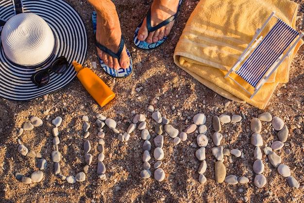 Vista dall'alto della spiaggia di sabbia sul mare, gli articoli da spiaggia sono disposti sulla sabbia. la parola estate è di pietra Foto Premium