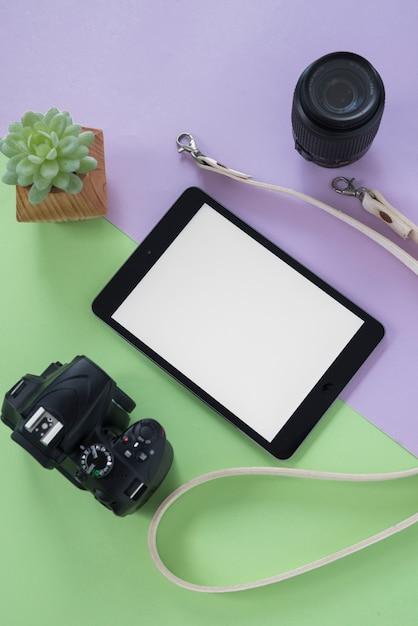 Vista dall'alto della tavoletta digitale con schermo vuoto; telecamera; lenti della macchina fotografica; cintura e pianta succulenta su doppio fondo Foto Gratuite