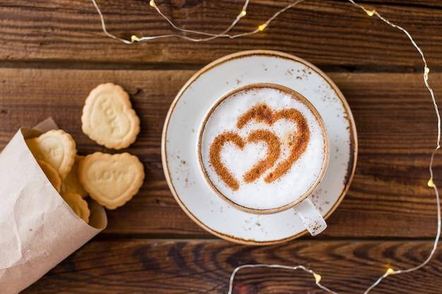 Vista dall'alto della tazza di caffè e biscotti a forma di cuore Foto Gratuite