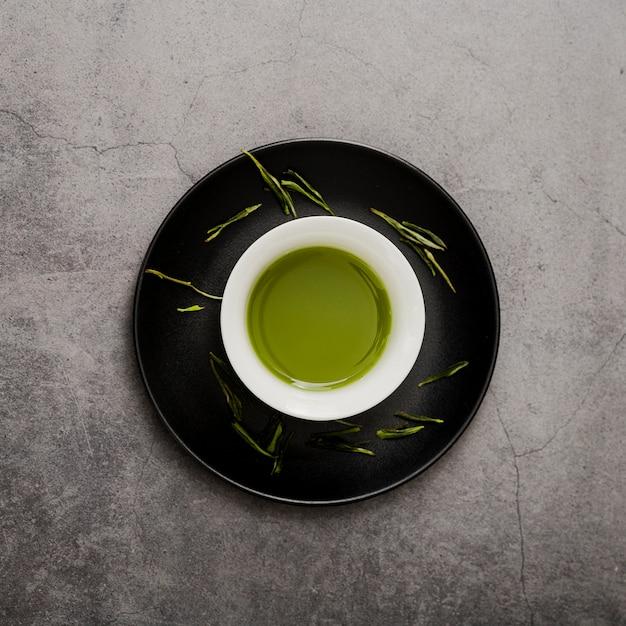 Vista dall'alto della tazza di tè matcha sul piatto Foto Gratuite