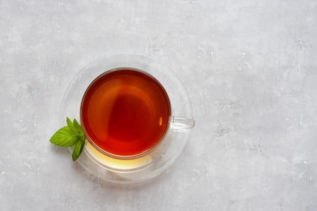 Vista dall'alto della tazza di vetro con tè sulla luce Foto Premium