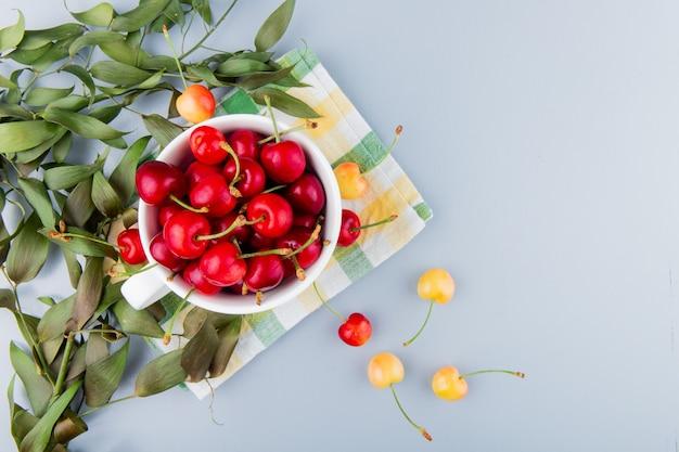 Vista dall'alto della tazza piena di ciliegie rosse sul lato sinistro e superficie bianca decorata con foglie con spazio di copia Foto Gratuite