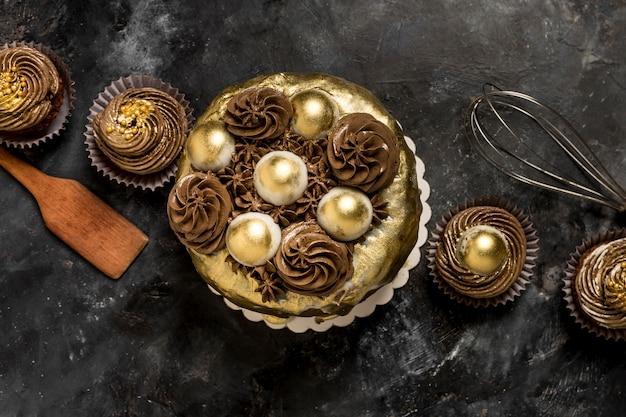 Vista dall'alto della torta con cupcakes e frusta Foto Gratuite