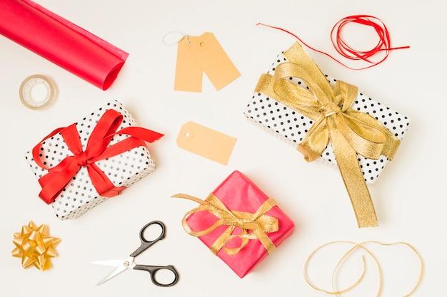 Vista dall'alto delle forniture di cancelleria; scatole regalo e etichette vuote su sfondo bianco Foto Gratuite
