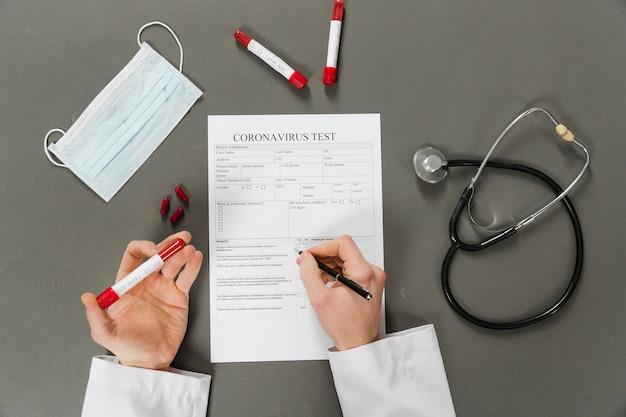 Vista dall'alto delle mani del medico compilando un test di coronavirus Foto Gratuite
