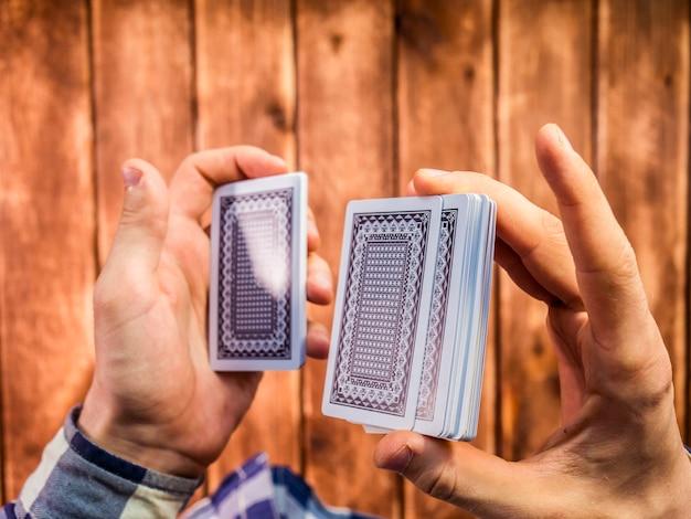 Vista dall'alto delle mani mescolando le carte da gioco sulla superficie in legno Foto Premium